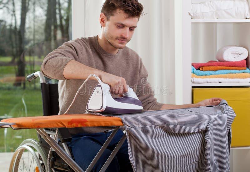 Hombre discapacitado durante planchar fotos de archivo libres de regalías