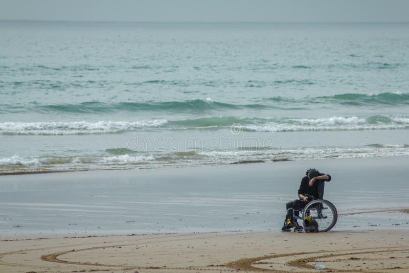 Hombre discapacitado en la silla de ruedas en la playa que mira el teléfono móvil fotografía de archivo