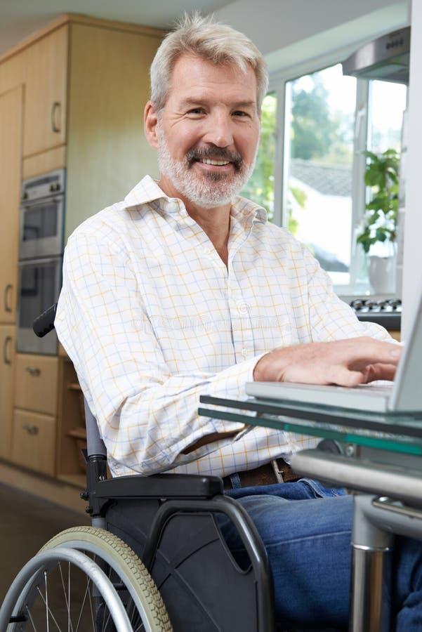 Hombre discapacitado en silla de ruedas usando el ordenador portátil en casa imagenes de archivo