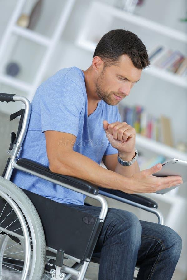Hombre discapacitado en silla de ruedas usando la tableta de Digitaces en casa foto de archivo libre de regalías