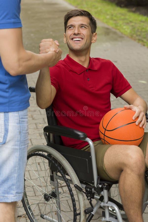 Hombre discapacitado feliz que lleva a cabo un baloncesto fotografía de archivo libre de regalías