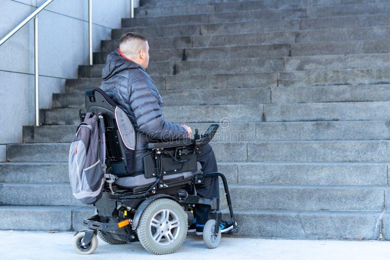 Hombre discapacitado joven en una silla de ruedas eléctrica delante de las escaleras fotografía de archivo libre de regalías
