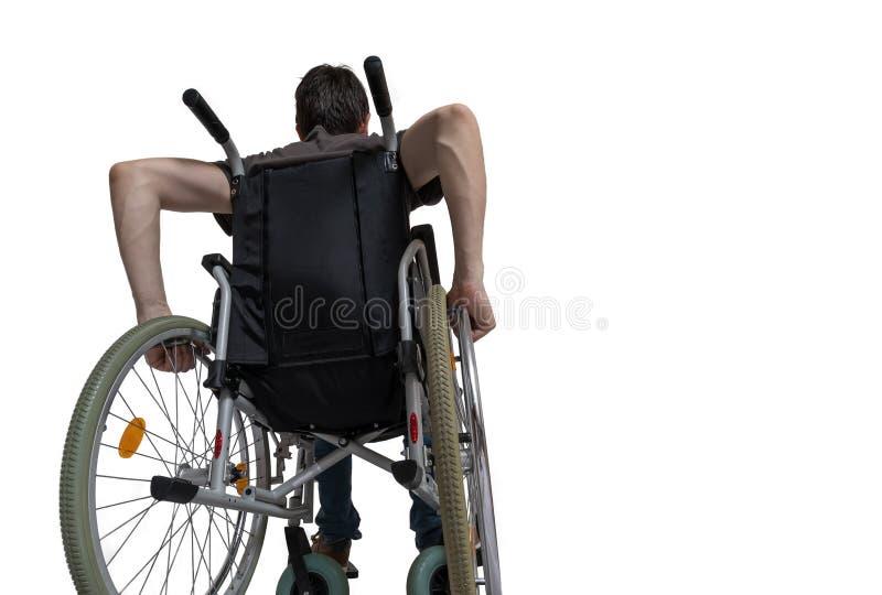 Hombre discapacitado perjudicado que se sienta en la silla de ruedas Aislado en el fondo blanco foto de archivo libre de regalías