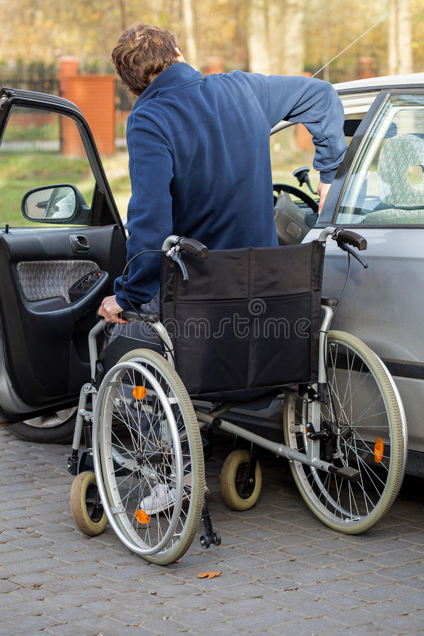 Hombre discapacitado que consigue en el coche fotos de archivo libres de regalías