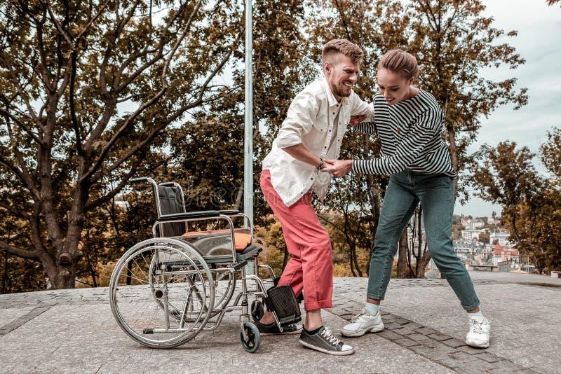 Hombre discapacitado que hace su mejor mientras que se levanta de la silla de ruedas foto de archivo