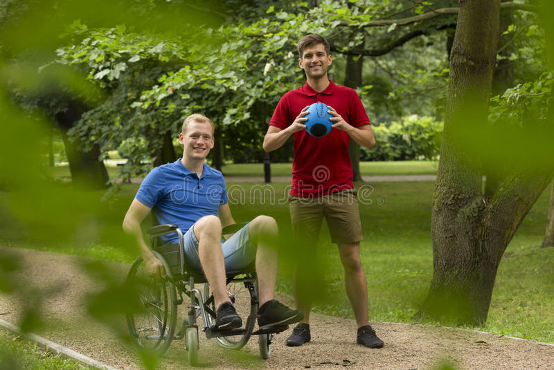 Hombre discapacitado que juega deporte con el amigo imágenes de archivo libres de regalías