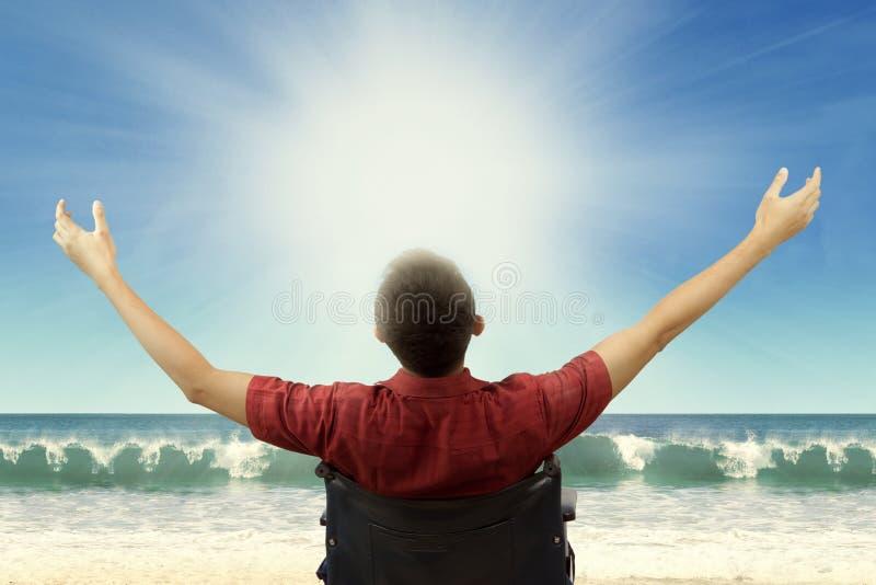 Hombre discapacitado que se sienta en weelchair en la playa foto de archivo libre de regalías