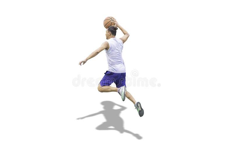 Hombre disponible aislado del baloncesto que salta en un fondo blanco con la trayectoria de recortes fotografía de archivo