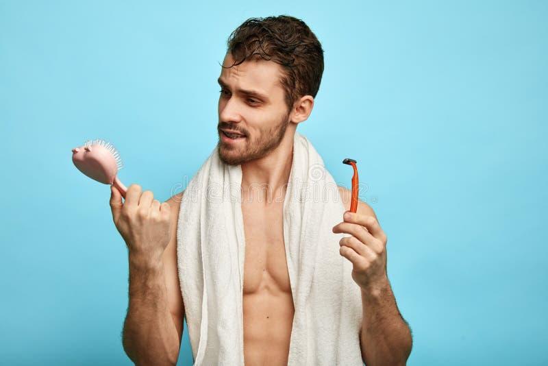 Hombre divertido agradable que sostiene un cepillo y una máquina de afeitar después de tomar el shover fotos de archivo