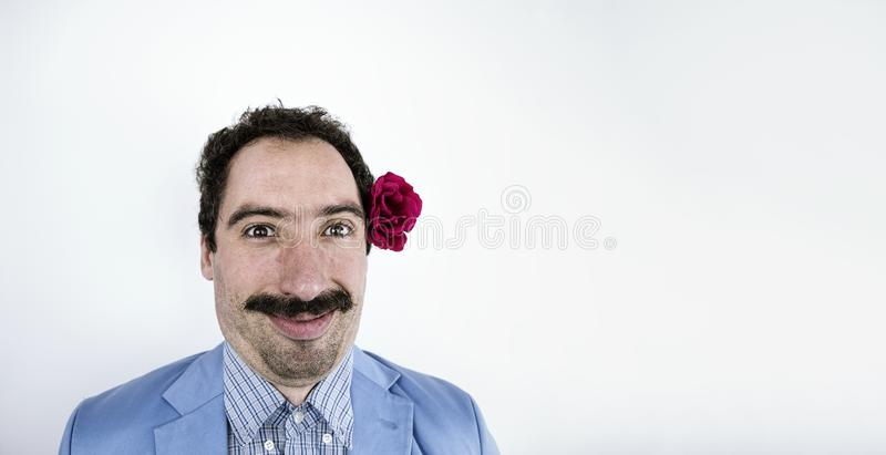 Hombre divertido con el bigote y la flor en el pelo en blanco fotos de archivo libres de regalías