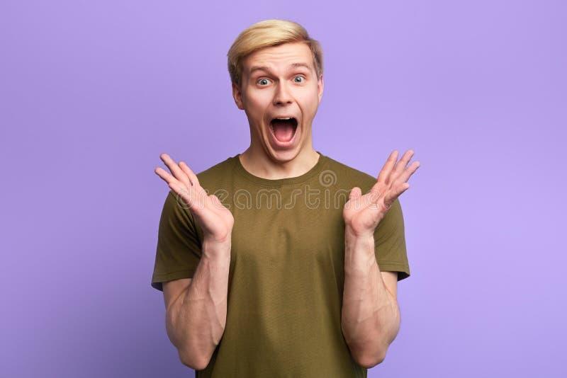 Hombre divertido con la expresión surprsied, siendo asustado para oír noticias horrorizadas foto de archivo
