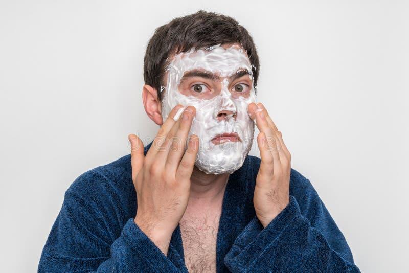 Hombre divertido con la máscara poner crema blanca natural en su cara fotografía de archivo libre de regalías