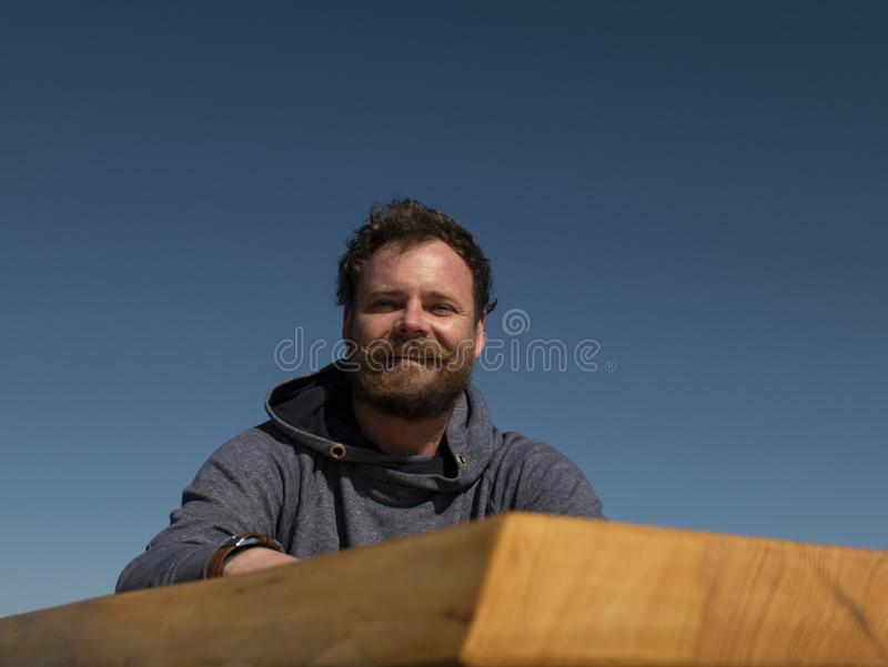 Hombre divertido con una barba y un bigote que se sientan en una mesa de centro contra un cielo azul foto de archivo