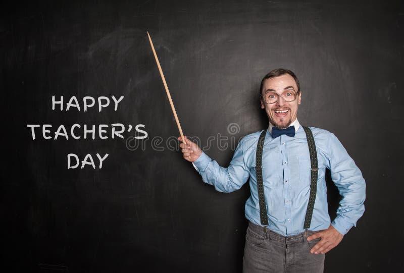Hombre divertido del profesor con el indicador D?a feliz de los profesores fotografía de archivo