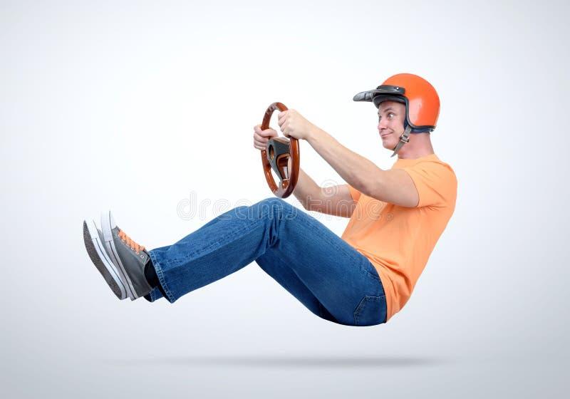 Hombre divertido en conductor de coche rojo del casco con el volante de madera, concepto auto fotos de archivo