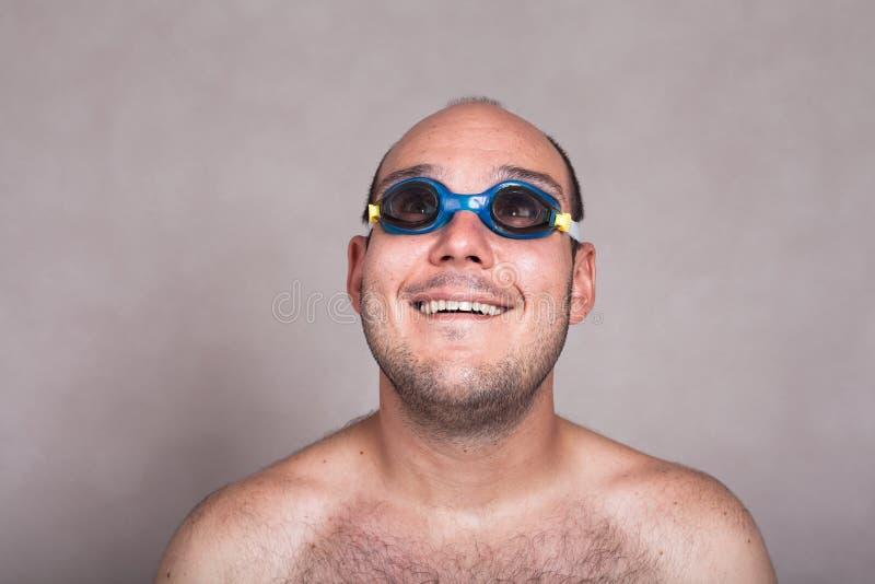 Hombre divertido en gafas de la natación que sueña despierto y que mira para arriba imagen de archivo