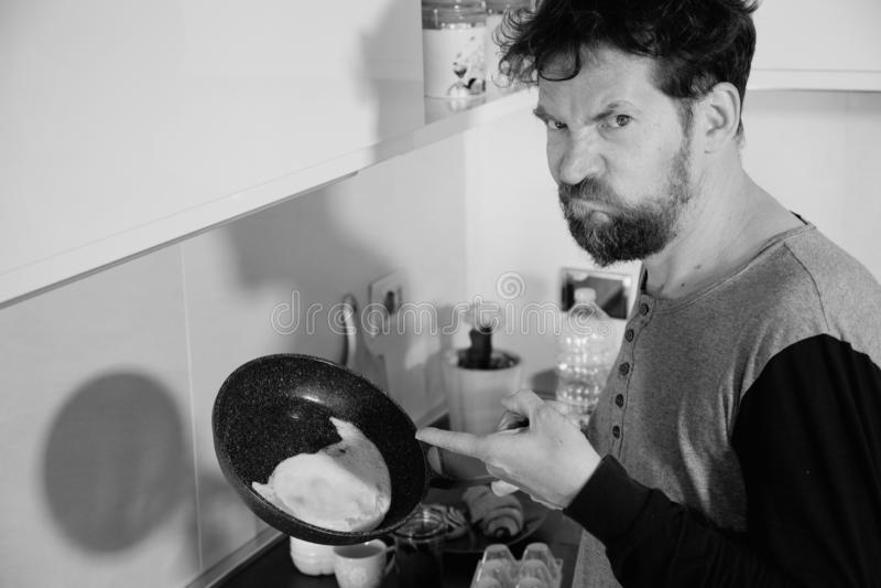 Hombre divertido en la cocina no capaz de cocinar un blanco y negro infeliz del huevo imagen de archivo