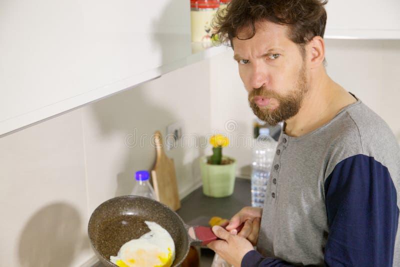 Hombre divertido en la cocina no capaz de cocinar un huevo imágenes de archivo libres de regalías