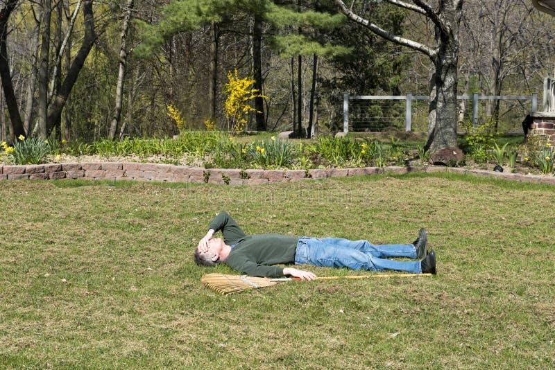 Hombre divertido enfermo y cansado de trabajo de yarda, trabajando imágenes de archivo libres de regalías