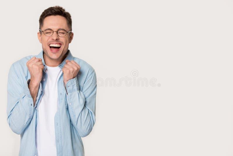 Hombre divertido extático que celebra la situación de la alegría a un lado en fondo gris fotos de archivo libres de regalías