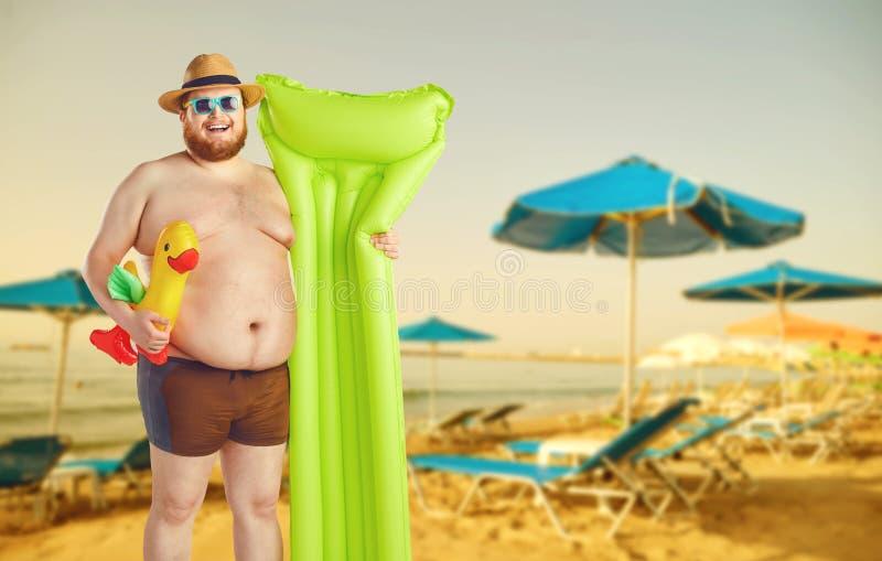 Hombre divertido gordo en troncos de natación con un colchón inflable en un fondo gris imagenes de archivo