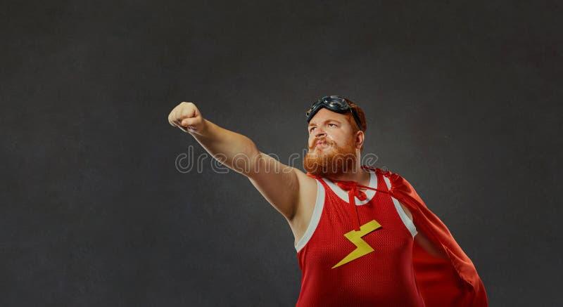 Hombre divertido gordo en un traje del super héroe fotografía de archivo libre de regalías