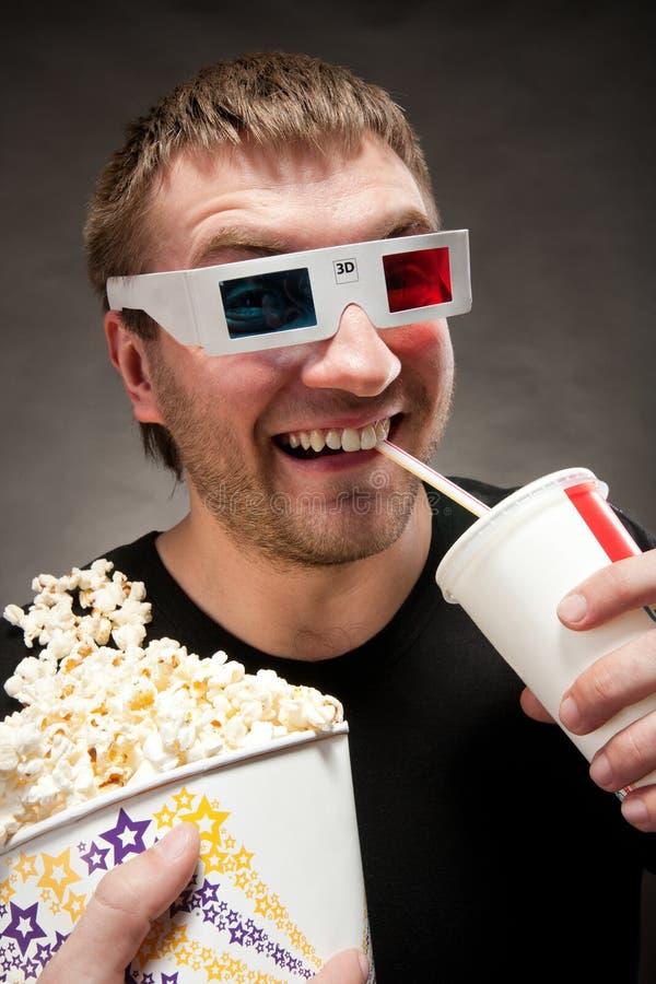 Hombre divertido que mira la película 3D foto de archivo