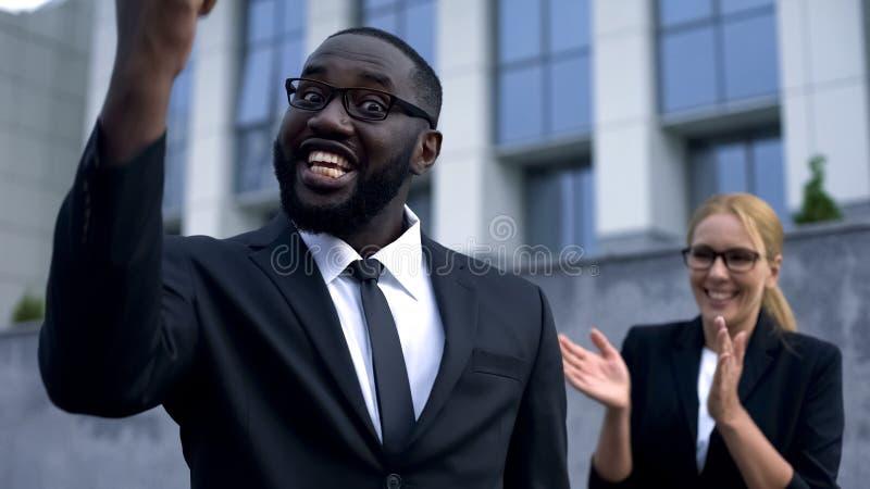 Hombre divertido que muestra sí la muestra, chocada con la buena victoria del negocio de los resultados financieros foto de archivo