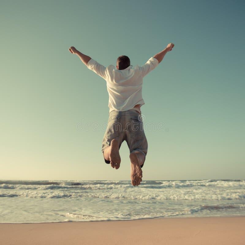 Hombre divertido que salta en la playa fotos de archivo