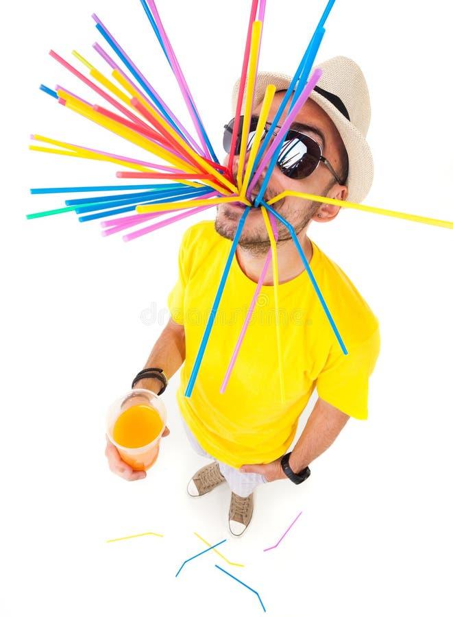 Hombre divertido que sostiene un vidrio de los vidrios de sol del jugo que llevan y de la camiseta amarilla en blanco fotografía de archivo