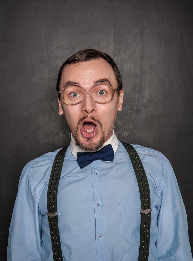 Hombre divertido sorprendido del profesor en la pizarra imagenes de archivo