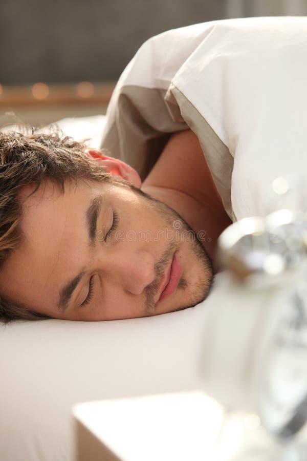 Hombre dormido en cama foto de archivo