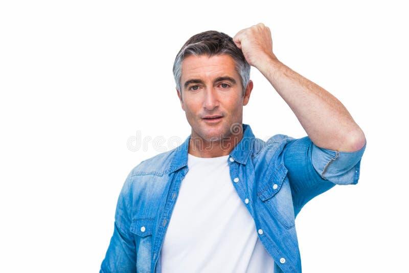 Hombre dudoso con su puño en la cabeza foto de archivo