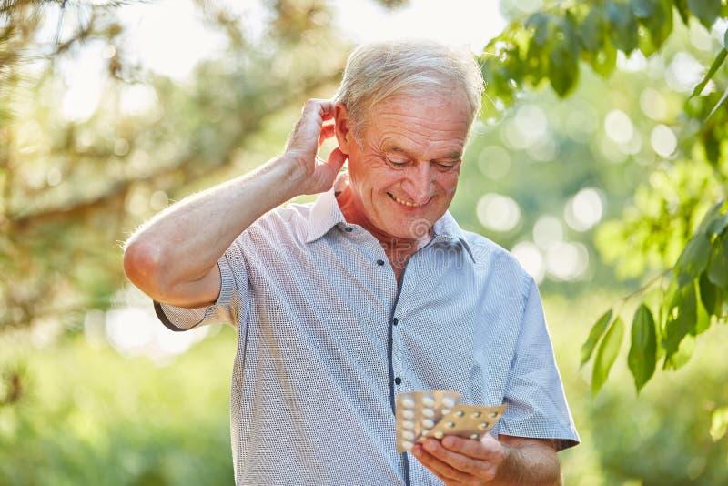Hombre dudoso mayor con la medicina en sus manos fotos de archivo