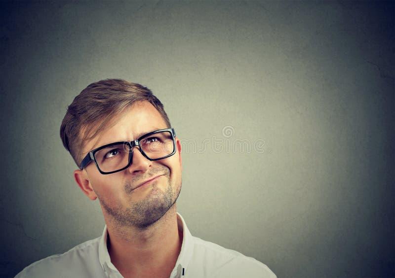 Hombre dudoso que mira para arriba en la reflexión imagen de archivo