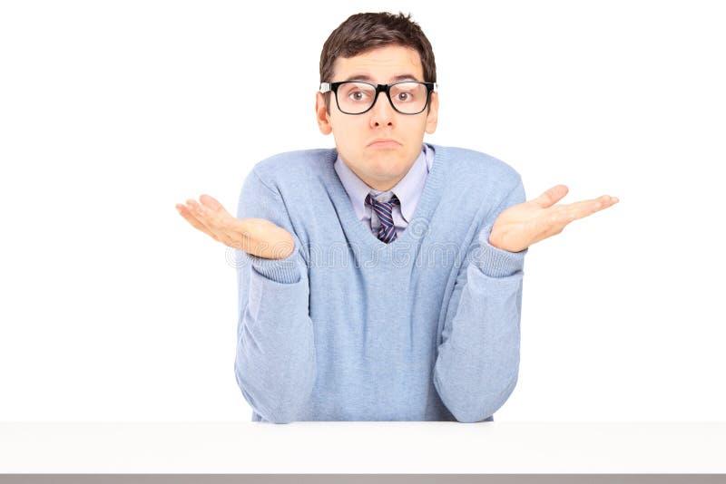 Hombre dudoso que se sienta y que gesticula con las manos imágenes de archivo libres de regalías