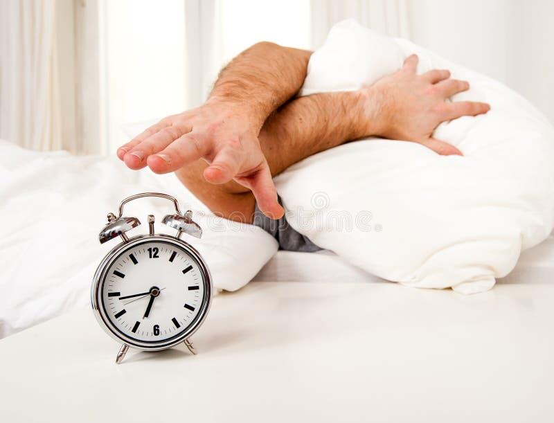 Hombre durmiente molestado por el mornin temprano del despertador imagenes de archivo