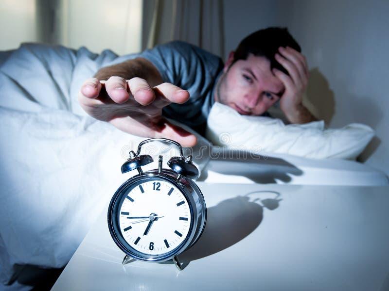 Hombre durmiente molestado por el mornin temprano del despertador fotografía de archivo