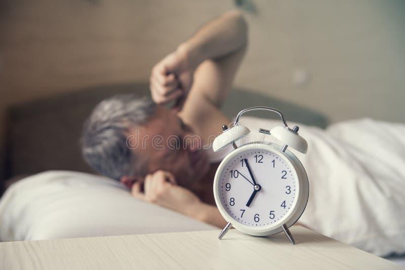 Hombre durmiente molestado por madrugada del despertador Hombre enojado en la cama despertada por un ruido imagenes de archivo