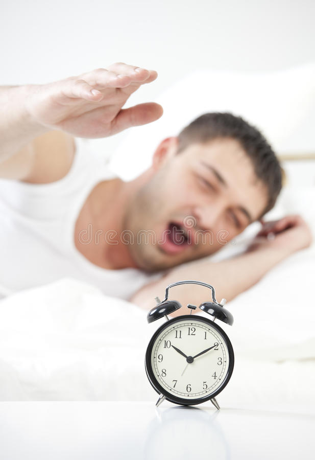 Hombre durmiente que alcanza para el reloj de alarma fotografía de archivo