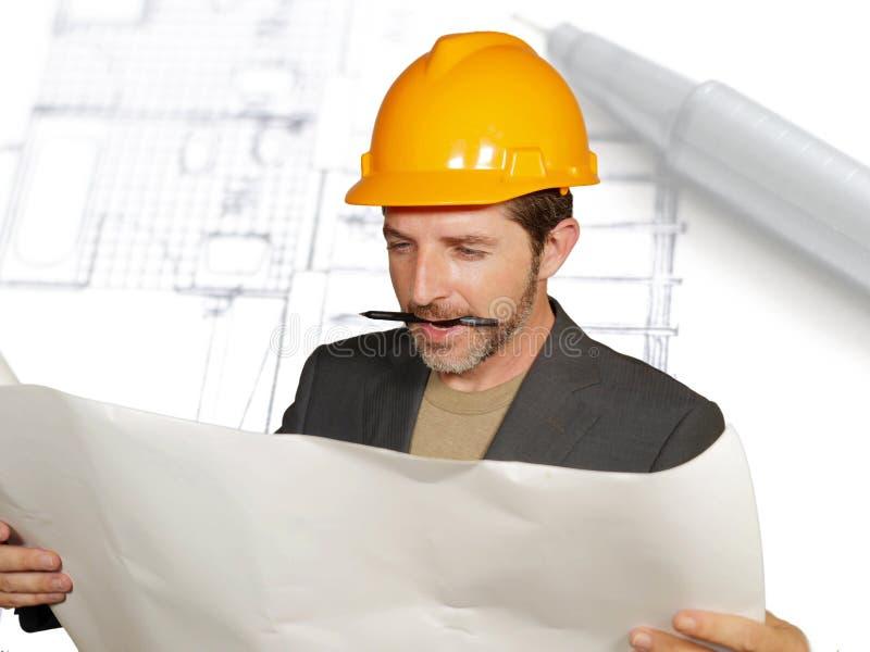 Hombre eficiente y confiado atractivo del arquitecto en casco del constructor que comprueba modelos de la construcción de edifici imagen de archivo libre de regalías