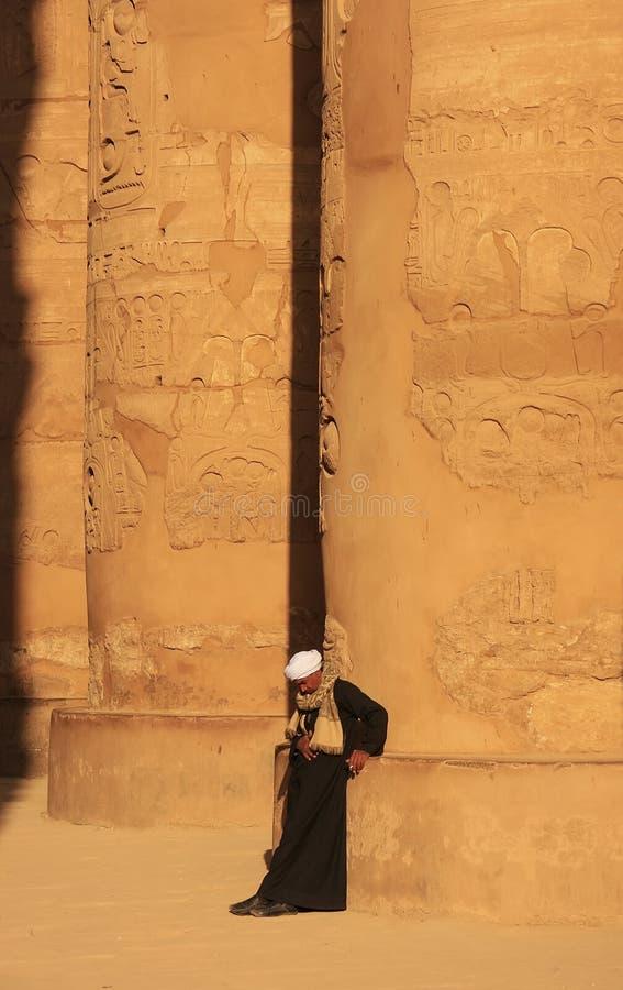 Hombre egipcio que se coloca en gran Pasillo hipóstilo, complejo del templo de Karnak, Luxor imágenes de archivo libres de regalías