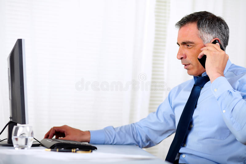 Hombre ejecutivo elegante que conversa en el teléfono celular imágenes de archivo libres de regalías