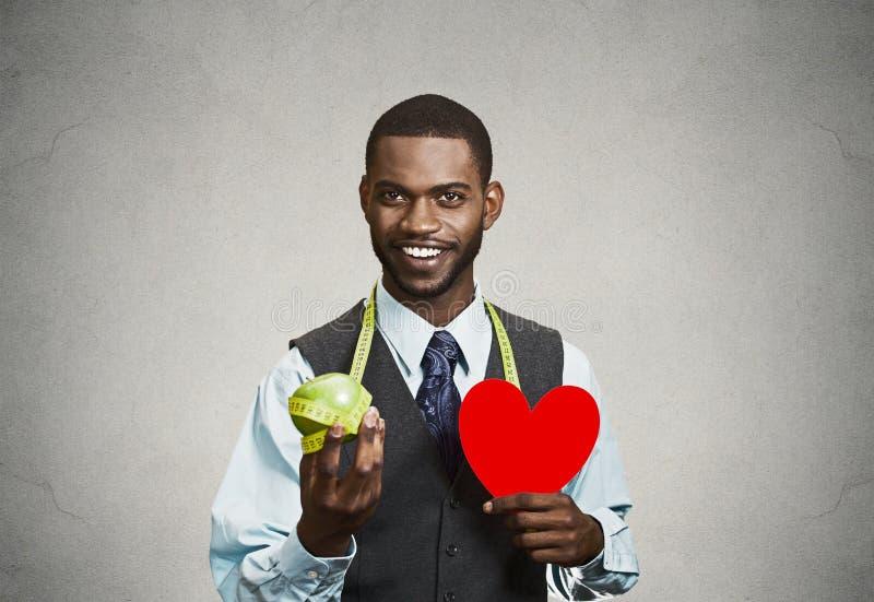 Hombre, ejecutivo empresarial que sostiene la manzana verde, corazón rojo imagen de archivo libre de regalías