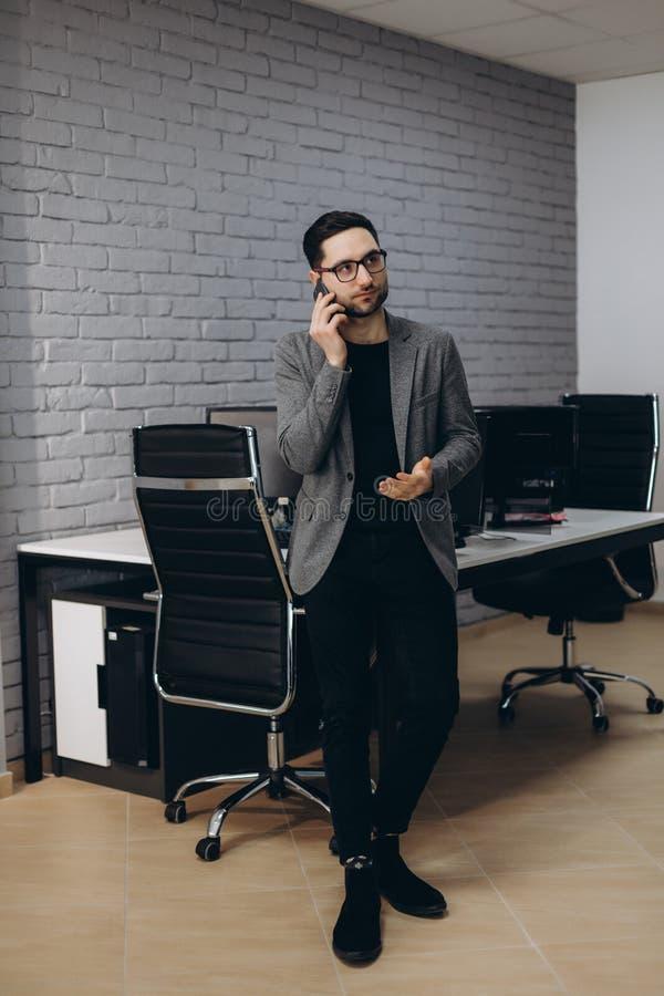 Hombre ejecutivo sonriente barbudo moreno joven hermoso atractivo del trabajador en el lugar de trabajo de la estación de trabajo imagenes de archivo