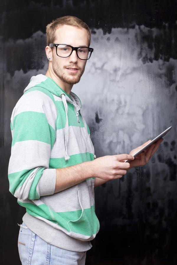 Hombre elegante apuesto del empollón con el ordenador de la tablilla foto de archivo