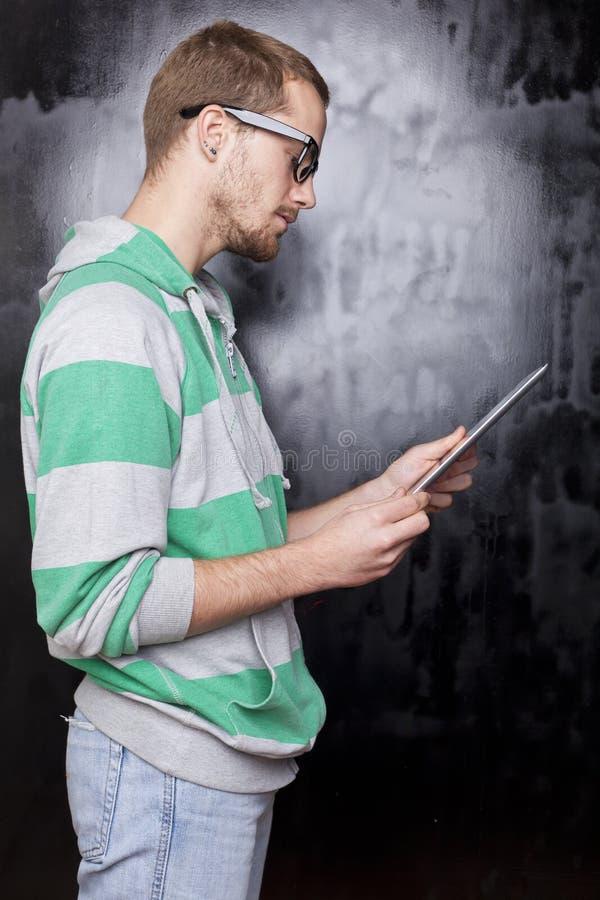 Hombre elegante apuesto del friki con el ordenador de la tablilla imágenes de archivo libres de regalías