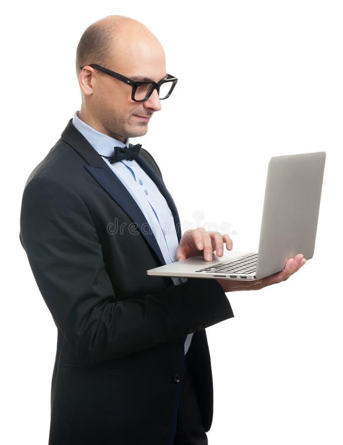 Hombre elegante calvo en traje y vidrios con el ordenador portátil foto de archivo