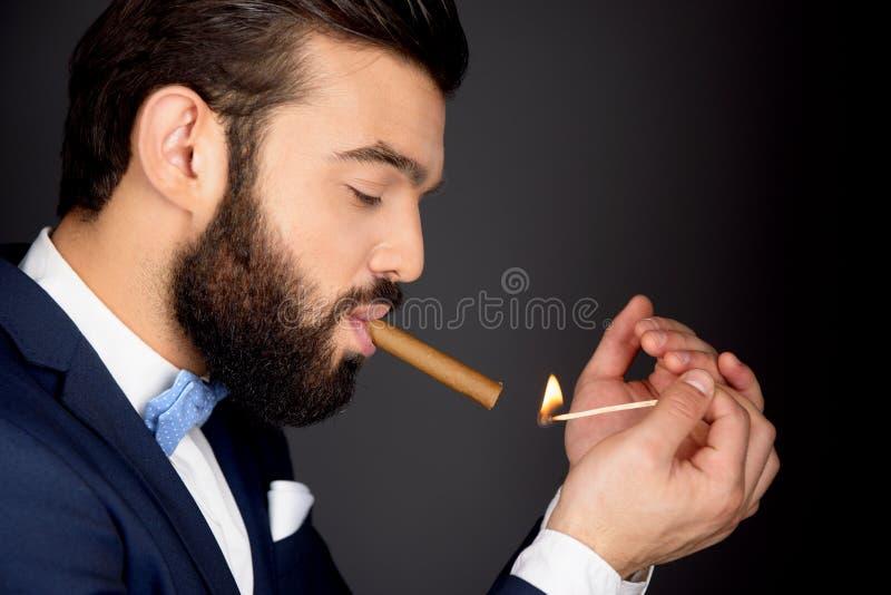 Hombre elegante con el cigarro de la iluminación de la barba fotografía de archivo