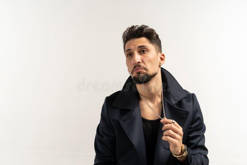 Hombre elegante con la barba en la chaqueta negra que presenta en la pared blanca fotografía de archivo